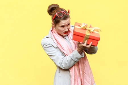 Hmm what is it! Cunning woman looking at gift box and want too open. Yellow background. Studio shot Stock Photo