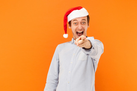 Hey you! Its new year! Attractive man pointing finger at camera, and toothy smiling. Focus on face. Studio shot, orange background Stock Photo