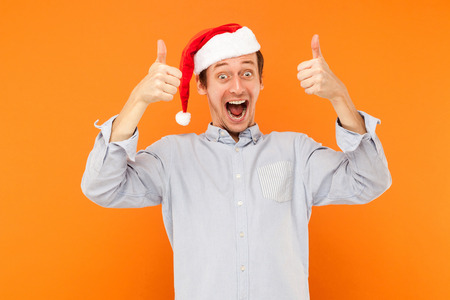 Man showing thumbs up, like sign. Holding many colorful bags after christmas shopping. Thumbs up and toothy smile. Indoor, studio shot on orange background