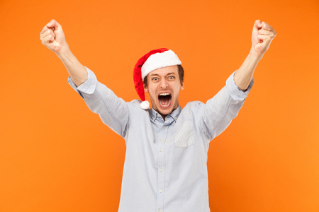 Im winner! Yes! Excited man hands up, shout and looking at camera with big eyes and open mouth. Studio shot, orange background