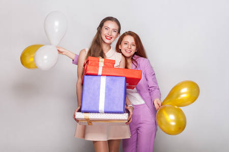 Two beautiful girl holding  gifts box and air balloon have a happiness look and showing a v sign at camera.  Studio shot Stock Photo