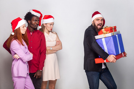 Happiness bearded man stole all gift box and runs away. Other people looking him anger and seriously. Studio shot