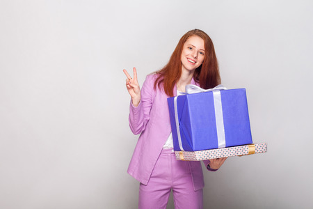 Ginger beautiful girl holding  gifts box and have a happy look and showing a v sign at camera. Studio shot