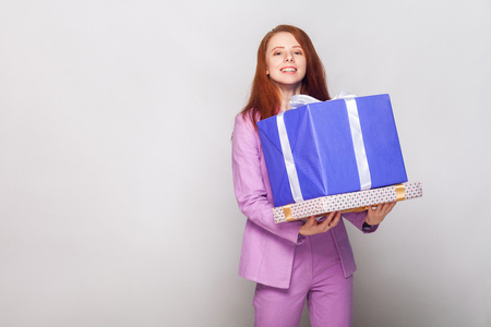 Happy birthday! Red haired cute girl holding her gifts and have a happy look. Studio shot Stock Photo
