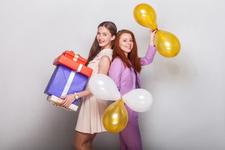 Beautiful girls standing back to back, holding many box and air balloon, toothy smiling and looking at camera. Studio shot, gray background