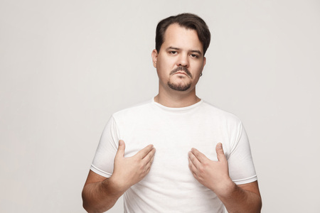 Arrogant and proud adult man pointing hands himself and looking at camera. Studio shot, gray wall