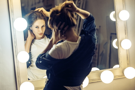 Beautiful young adult freckles woman looking at her reflection in a dressing room mirror. Studio shot