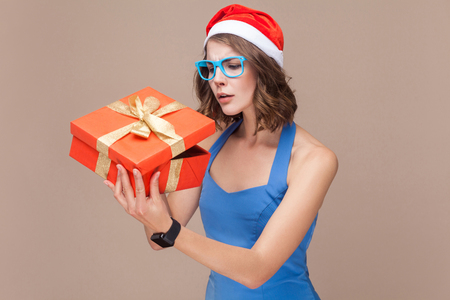 Cunning businesswoman looking at gift box and want too open. Brown background. Studio shot Stock Photo