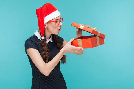Cunning businesswoman looking at gift box and want too open. Blue background. Studio shot Stock Photo