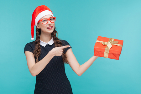 Business woman pointing finger on gift box and looking at camera and toothy smile. On green background. Studio shot