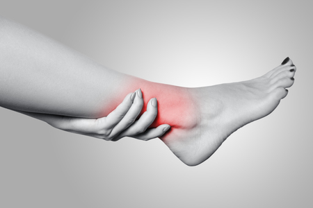 Closeup view of a young woman with pain on leg on gray background. Black and white photo with red dot. Stock Photo