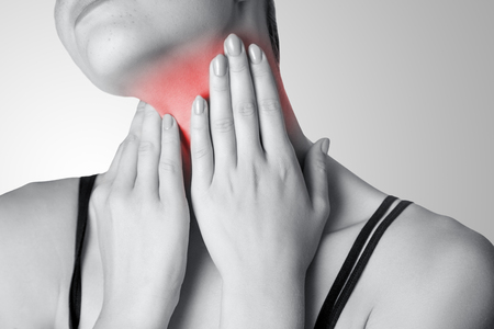 Closeup view of a young woman with pain on neck or thyroid gland on gray background. Black and white photo with red dot.