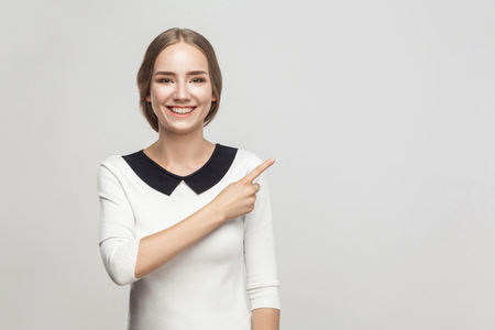 Business woman pointing finger at copy space, toothy smiling and looking at camera. Studio shot, gray background Stock Photo