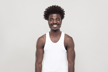 Happiness afro man looking at camera and toothy smiling. Studio shot. Gray background Stock Photo