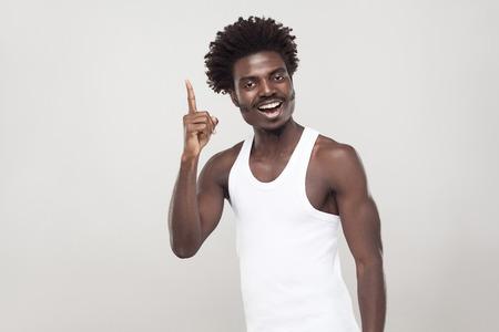 Goed idee! Afro man vinger omhoog en toothy glimlachen. Binnenschot, grijze muur