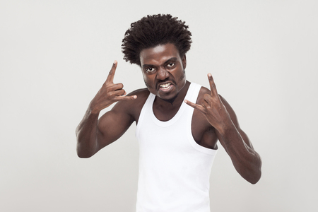 Aggressive afro man showing rock sign, looking at camera. Studio shot. Gray background