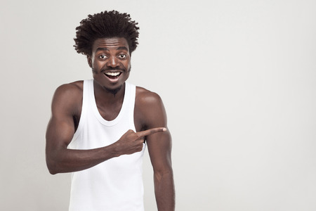 Amazement afro man, pointing finger at copy space. Studio shot. Gray background