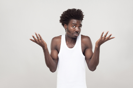 Emotional afro man have a confused look. Studio shot. Gray background Stock Photo