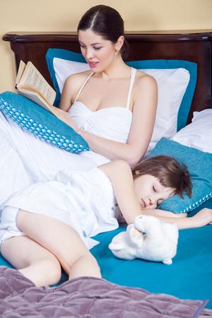 bedtime story: Child sleeping, mom read book. Studio shot