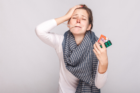 Young adult sick woman have temperature, holding many pills. Studio shot, isolated on gray background