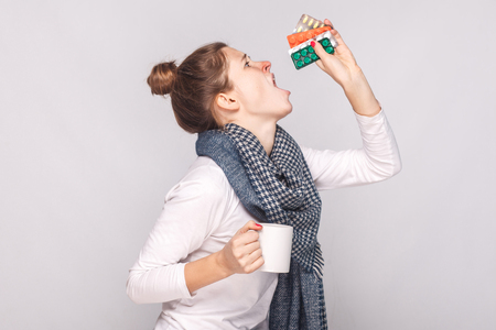 Sick young woman holding cup with tea, many pills and antibiotics. Studio shot, isolated on gray background