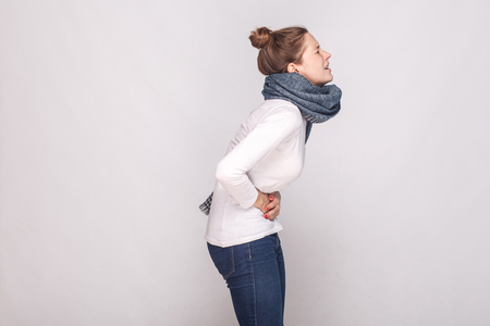 Side view. Periods, monthly, monthlies concept. Young woman have a stomach. Studio shot Stock Photo