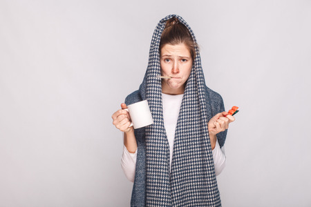 Young woman with gray scarf, holding cup, thermometer and pills. Indoor shot. Stock Photo