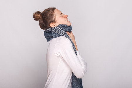 Profile view sick woman touching her neck, have cough, sore throat. Studio shot