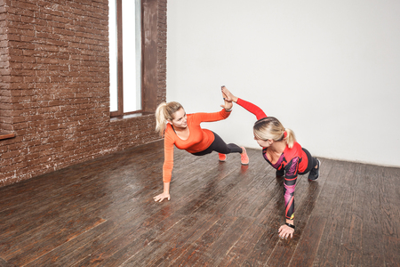 We did it! Best friends doing pilates each other. Studio shot Stock Photo