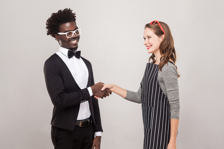 African man and freckles caucasian woman handshake and toothy smiling. Studio shot Фото со стока
