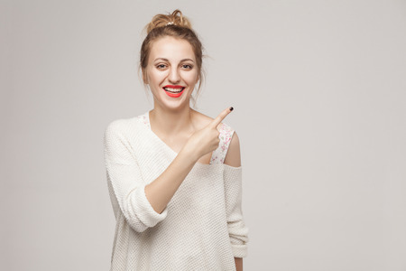 Successful blonde woman pointing finger at copy space and smiling.Studio shot, gray wall