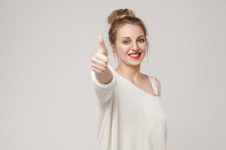 Young adult woman thumbs up, looking at camera with toothy smile. Studio shot, isolated on gray background