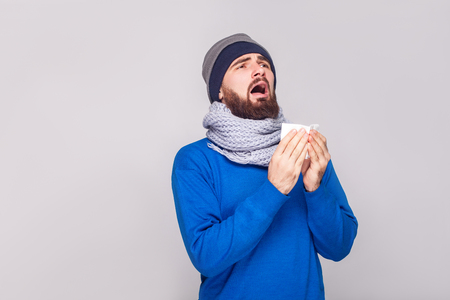 Sick bearded woman open mouth, holds a handkerchief and sneezes. Studio shot, isolated on gray background