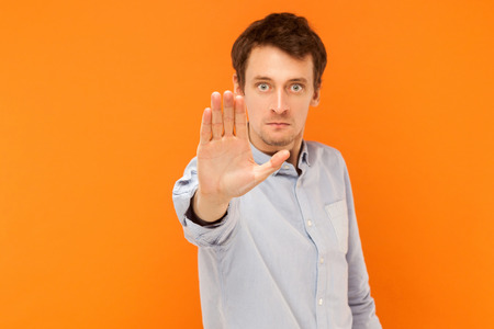 Stop hand. Focus on hand. Body language. Studio shot, orange background