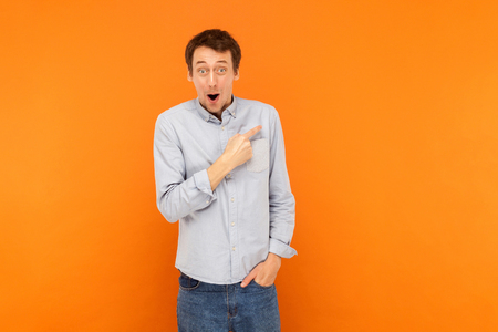 Amazement man pointing finger at copy space, open mouth and looking at camera. Have a surprised look . Studio shot, orange background