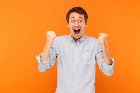 Victory! Successful businessman have a happiness look. Big eyes and open mouth and looking at camera. Studio shot, orange background