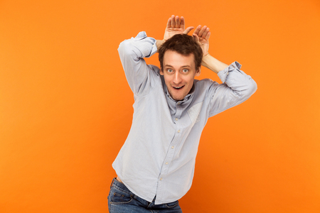 Attractive business man, to be bunny and have a funny look. Studio shot, orange background