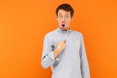 Who, im? Shocked man looking at camera and pointing finger himself. Studio shot, orange background