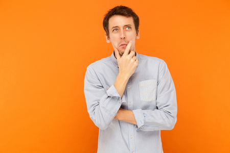 Hmm, im need thinking. Young adult man looking up, holding chin and musing. Indoor shot. Isolated on orange background