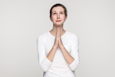 종교 개념입니다. 기도 소녀. 회색 배경에 고립 된 스튜디오 샷