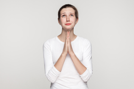 Religion concept. Prayer girl. Studio shot,isolated on gray background