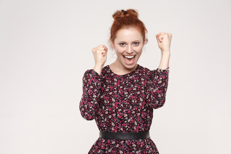 Win and success concept. Redhead woman rejoicing for his success. Isolated on gray  background. Indoor, studio shot