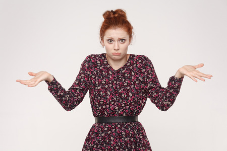 Negative human emotions, facial expressions, life perception and attitude. Puzzled  redhead woman with arms out, shrugging her shoulders. Isolated studio shot on gray background. Stock Photo