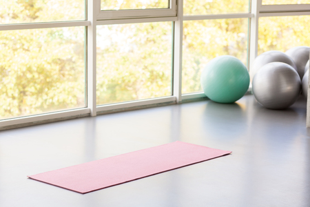 Yoga mat lie on gray floor near window and fitball. Studio shot