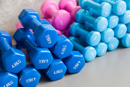 Blue and pink dumbbells lie on the gray floor. Studio shot