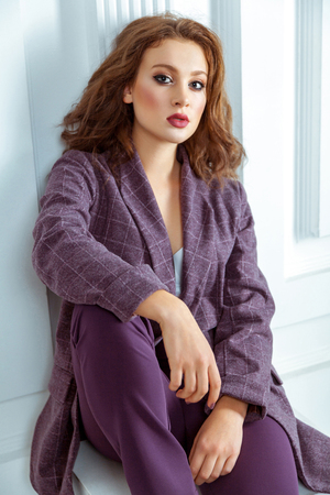 Seductive girl in the purple suit looking at camera. Luxurious lifestyle. Fashion, beauty. Studio shot Stock Photo
