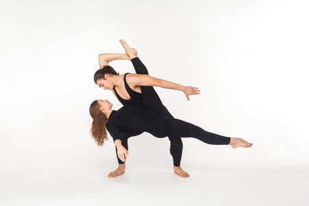 Two flexibility friends dancing, doing performance. Studio shot, isolated on white background