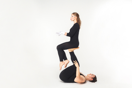 Acrobatic concept, sit pose. Young man holding woman legs, balancing. Studio shot, isolated on white background Stock Photo