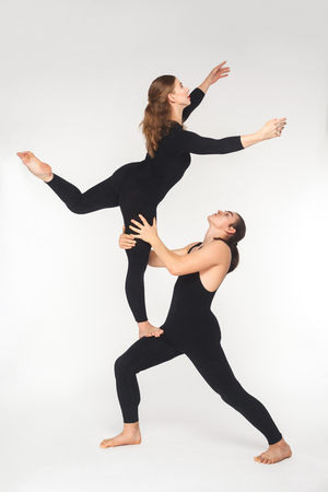 Young adult couple doing acroyoga pose for practicing in balance. Studio shot, isolated on white background
