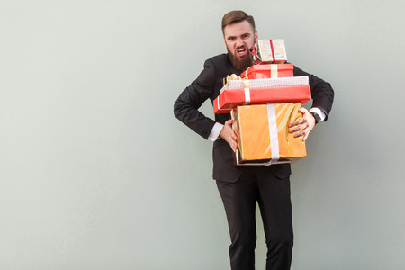 Angry and crazy boss holding boxes and shout at camera. Studio shot Stock Photo